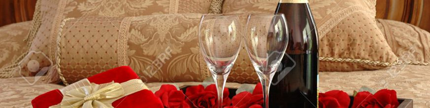 664312-gifts-champagne-and-roses-on-a-bed-stock-photo